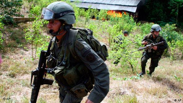 Anti narcotics police officers leave a coca field after burning a laboratory to make cocaine in San Miguel, on Colombia's southern border with Ecuador