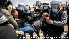 Security forces arrest a teacher as they disperse a protest demanding permanent employment, in Rabat, Morocco, Wednesday, April 7, 2021. Teachers have been protesting in Morocco to end the hiring of newly graduated teachers on temporary renewable contracts. (AP Photo/Mosa'ab Elshamy)