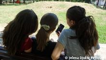 Nis. 12.08.2021. Children aged 12 to 18 play with a cell phone while sitting on a park bench in Nis