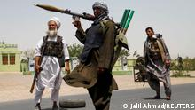 FILE PHOTO: Former Mujahideen hold weapons to support Afghan forces in their fight against Taliban, on the outskirts of Herat province, Afghanistan July 10, 2021. REUTERS/Jalil Ahmad/File Photo