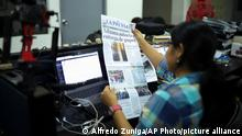 A journalist holds up a copy of La Prensa independent newspaper with a headline that reads in Spanish; Customs authorizes release of printing paper, in Managua, Nicaragua, Friday, Feb. 7, 2020. La Prensa had announced Wednesday that the government had agreed to unblock the newspaper's printing materials held up since August 2018. It said the Vatican's top diplomat in Managua, Waldemar Stanislaw Sommertag, had intervened on its behalf. (AP Photo/Alfredo Zuniga)