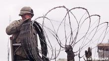 (FILES) In this file photo a US Marine is given a hand using barbed wire to secure the walls the US embassy in Kabul on January 11, 2002. - The United States said on August 12, 2021 it was sending troops to the international airport in Afghanistan's capital Kabul to pull out US embassy staff as the Taliban makes rapid gains.We are further reducing our civilian footprint in Kabul in light of the evolving security situation, State Department spokesman Ned Price told reporters.This president prioritizes above all else the safety and security of Americans who are serving overseas, he said of Joe Biden, who has ordered a withdrawal of US troops from Afghanistan after nearly 20 years. (Photo by ROB ELLIOTT / AFP)