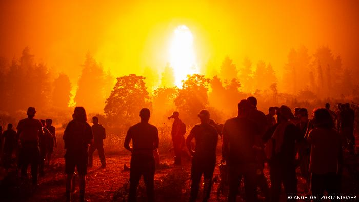 People gather in an open field and wait to support firefighters during a wildfire next to the village of Kamatriades, near Istiaia, northern Evia (Euboea) island on August 9, 2021