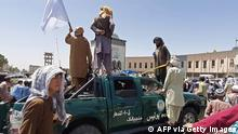 Taliban fighters stand over a damaged police vehicle along the roadside in Kandahar on August 13, 2021. (Photo by - / AFP) (Photo by -/AFP via Getty Images)