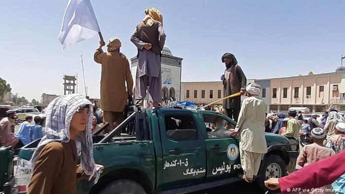 Los combatientes talibanes festejan la conquista de Kandahar sobre un vehículo de la Policía.