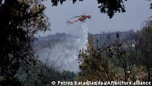 Ein Hubschrauber wirft Wasser über einem Feuer im Dorf Avgaria auf der Insel Euböa ab. In Griechenland hat sich die Lage bei den Großbränden leicht entspannt. Auf der zweitgrößten griechischen Insel Euböa gab es am Mittwoch, 11.08.2021, weiterhin viele, aber kleinere Brände. +++ dpa-Bildfunk +++