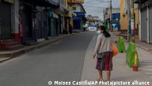 A resident walks past closed stores on the second day of a four-day lockdown, decreed by local authorities to help curb the spread of COVID-19 in the Kaqchikel Indigenous town of San Martin Jilotepeque, Guatemala, Friday, July 9, 2021. On Thursday, Guatemala announced its highest number of infections since the pandemic began, with 3,000 infected in a single day. (AP Photo/Moises Castillo)