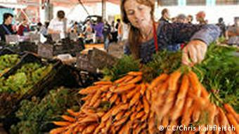 A woman stacks a fresh bunch of carrots for sale at a farmer's market.