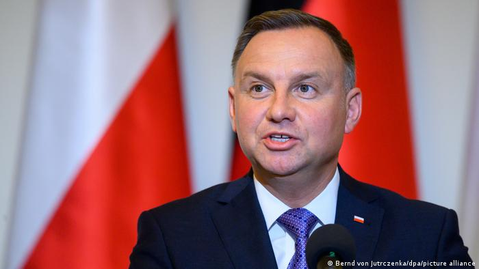 Polish President Andrzej Duda before the red and white Polish flag