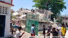 People stand outside the residence of the Catholic bishop after it was damaged by an earthquake in Les Cayes, Haiti, Saturday, Aug. 14, 2021. (AP Photo/Delot Jean)