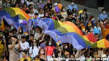 People march with a rainbow flag as they take part in the Pride Parade in Bucharest on August 14, 2021. - Thousands of members and supporters of the LGBT community took part in the march in downtown Bucharest to celebrate the diversity. (Photo by Daniel MIHAILESCU / AFP) (Photo by DANIEL MIHAILESCU/AFP via Getty Images)