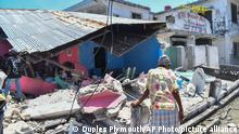 A woman stands in front of a destroyed home in the aftermath of an earthquake in Les Cayes, Haiti, Saturday, Aug. 14, 2021. A 7.2 magnitude earthquake struck Haiti on Saturday, with the epicenter about 125 kilometers ( 78 miles) west of the capital of Port-au-Prince, the US Geological Survey said. (AP Photo/Duples Plymouth)