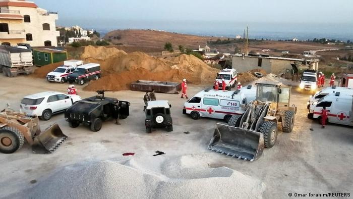 Автомобили врачей и экскаваторы на месте взрыва в Ливане