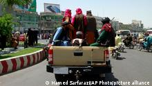 Taliban fighters sit on the back of a vehicle in the city of Herat, west of Kabul, Afghanistan, Saturday, Aug. 14, 2021, after they took this province from Afghan government. The Taliban seized two more provinces and approached the outskirts of Afghanistan's capital. (AP Photo/Hamed Sarfarazi)