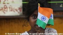 NEW DELHI, INDIA - 2021/08/14: A child holds Indian national flags for sale as she waits for the customer on the roadside ahead of Indian 75th Independence Day celebrations. Indian Prime Minister Narendra Modi will address the nation from the ramparts of the historic Red Fort on August 15th (Sunday) to mark the 75 years of Independence. (Photo by Naveen Sharma/SOPA Images/LightRocket via Getty Images)
