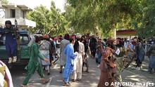 Taliban fighters and local people are pictured along the street in Jalalabad province on August 15, 2021. (Photo by - / AFP) (Photo by -/AFP via Getty Images)