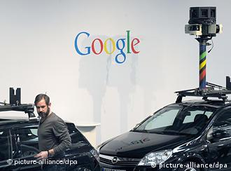 A car used in the Street View project with a camera attached is parked next to the Google logo