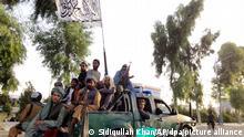 14.08.2021, Afghanistan, Kandahar: Schwer bewaffnete Taliban-Kämpfer patrouillieren in einem Polizeifahrzeug in Kandahar. Die Taliban haben in der Nacht zum 13.08.2021 (Ortszeit) die zweitgrößte Stadt Kandahar im Süden von Afghanistan eingenommen. Foto: Sidiqullah Khan/AP/dpa +++ dpa-Bildfunk +++