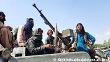 15.08.2021, Afghanistan, Kandahar: Schwer bewaffnete Taliban-Kämpfer fahren in einem Fahrzeug durch Mehtarlam, der Hauptstadt der Provinz Laghman. Foto: Str/XinHua/dpa +++ dpa-Bildfunk +++