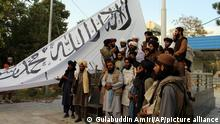 Taliban fighters poses for a photograph while raising their flag Taliban fighters raise their flag at the Ghazni provincial governor's house, in Ghazni, southeastern, Afghanistan, Sunday, Aug. 15, 2021. (AP Photo/Gulabuddin Amiri)