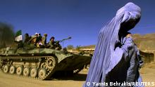 FILE PHOTO: An Afghan woman wearing a traditional burqa walks on the side of a road as a Northern Alliance APC, (Armoured Personnel Carrier) carrying fighters and the Afghan flag, drives to a new position in the outskirts of Jabal us Seraj, some 60kms north of the Afghan capital Kabul November 4, 2001. REUTERS/Yannis Behrakis/File Photo