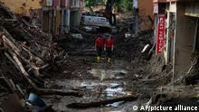 Rescue workers walk in a street in Bozkurt town of Kastamonu province, Turkey, Sunday, Aug. 15, 2021, after flooding. Turkey sent ships to help evacuate people and vehicles from a northern town on the Black Sea that was hard hit by flooding, as the death toll in the disaster rose Sunday to at least 62 and more people than that remained missing. (AP Photo)