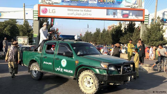 Combatentes do Talibã conduzem um veículo da polícia do lado de fora do aeroporto de Cabul