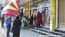 Workers at a beauty salon strip large photos of women off the wall in Kabul on Aug. 15, 2021, following news that the Taliban swept into the Afghan capital. (Kyodo)