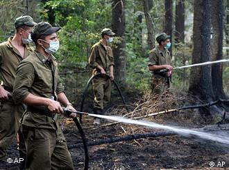 Soldiers spray water from hoses in a forest