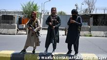 Taliban fighters stand guard along a street in Kabul on August 16, 2021, after a stunningly swift end to Afghanistan's 20-year war, as thousands of people mobbed the city's airport trying to flee the group's feared hardline brand of Islamist rule. (Photo by Wakil Kohsar / AFP) (Photo by WAKIL KOHSAR/AFP via Getty Images)