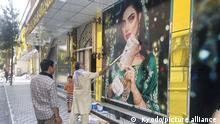 A worker at a beauty salon paints over a large photo of a woman on the wall in Kabul on Aug. 15, 2021, following news that the Taliban swept into the Afghan capital. (Kyodo)