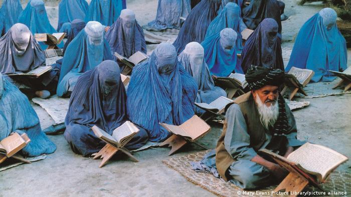 Filmszene Fünf Uhr am Nachmittag: In mehreren Reihen hintereinander sitzen Frauen in Burkas auf Matten hinter kleinen Buchständern und lesen. In der ersten Reihe sitzt ein alter bärtiger Mann alleine und liest ebenfalls.