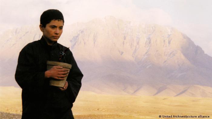 Filmszene aus 'Osama' (2003) - eine junge Person steht in einer kahlen Berglandschaft. undhält einen Blumentopf in den Händen