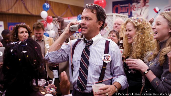 Szene aus Der Krieg des Charlie Wilson - Tom Hanks spricht in ein großes drahtloses Telefon während einer Wahlparty, im Hintergrund lachen viele Personen