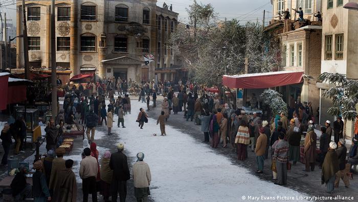 Szene aus Der Drachenläufer: Menschen stehen am Rande eines schneebedeckten Pfades, während Kinder Drachen steigen lassen.