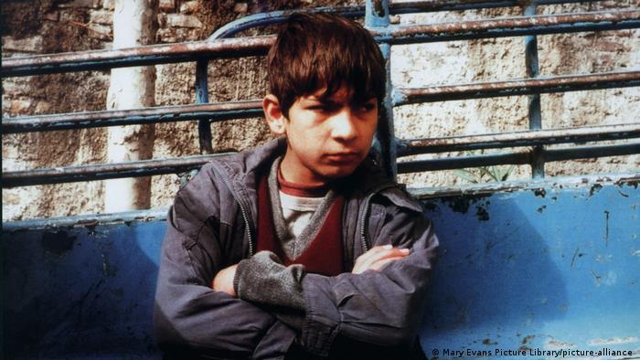 Szene aus In This World: Ein ernst blickender Junge lehnt mit verschränkten Armen an einer Mauer.