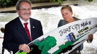 Petra Offermann presents Munich Mayor Christian Ude with a surfboard as a gift of thanks