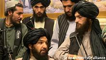 Taliban-Kämpfer sitzen und stehen in einem Raum des afghanischen Präsidentenpalastes. Nur wenige Stunden nach der Flucht des afghanischen Präsidenten Ghani haben Kämpfer der militant-islamistischen Taliban den Präsidentenpalast in der Hauptstadt Kabul eingenommen. +++ dpa-Bildfunk +++