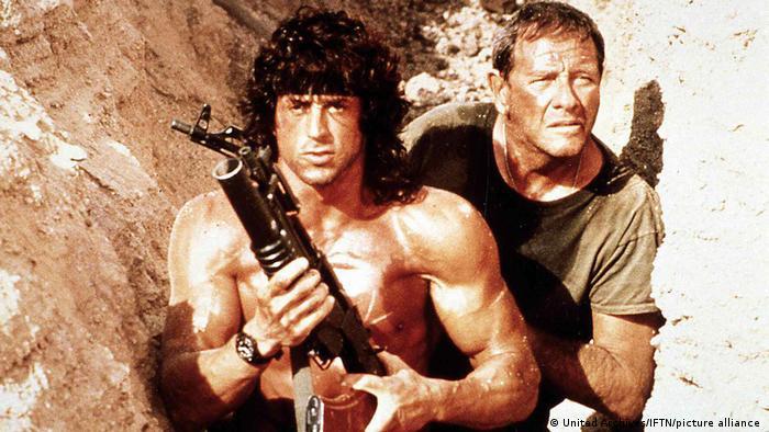 Szene aus Rambo III (1988), Rambo mit einer Waffe im Anschlag und einer weiteren Person hinter ihm zwischen Felsgestein.