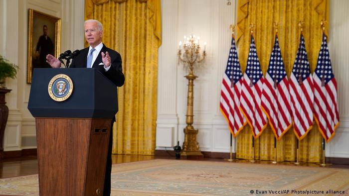 Biden está à esquerda da foto, em pé, atrás de um púlpito. Ao fundo, à direita, há cinco bandeiras dos EUA.