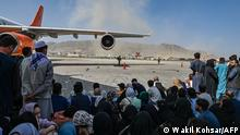 Afghan people sit as they wait to leave the Kabul airport in Kabul on August 16, 2021, after a stunningly swift end to Afghanistan's 20-year war, as thousands of people mobbed the city's airport trying to flee the group's feared hardline brand of Islamist rule. (Photo by Wakil Kohsar / AFP)