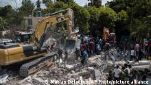 A bulldozer removes debris at the site of the collapsed Hotel Le Manguier in Les Cayes, Haiti, Monday, Aug. 16, 2021, two days after a 7.2-magnitude earthquake struck the southwestern part of the country. (AP Photo/Matias Delacroix)