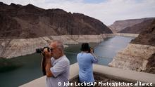 People take pictures of Lake Mead near Hoover Dam at the Lake Mead National Recreation Area, Friday, Aug. 13, 2021, in Arizona. The bathtub ring of light minerals shows the high water mark of the reservoir which has fallen to record lows. (AP Photo/John Locher)