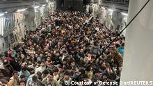 Evacuees crowd the interior of a U.S. Air Force C-17 Globemaster III transport aircraft, carrying some 640 Afghans to Qatar from Kabul, Afghanistan August 15, 2021. Picture taken August 15, 2021. Courtesy of Defense One/Handout via REUTERS. NO RESALES. NO ARCHIVES, THIS IMAGE HAS BEEN SUPPLIED BY A THIRD PARTY. MANDATORY CREDIT