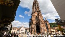 Menschen stehen auf dem Freiburger Münsterplatz vor dem Münster. Das Freiburger Münster ist formell eine Kathedrale, da Freiburg seit dem Jahr 1827 Bischofssitz ist. Die Erzdiözese Freiburg wurde am 16. August 1821 von Papst Pius VII. durch die Bulle «Provida solersque» formell errichtet. +++ dpa-Bildfunk +++