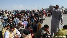Afghan passengers sit as they wait to leave the Kabul airport in Kabul on August 16, 2021, after a stunningly swift end to Afghanistan's 20-year war, as thousands of people mobbed the city's airport trying to flee the group's feared hardline brand of Islamist rule. (Photo by Wakil Kohsar / AFP)