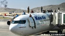 Afghan people climb atop a plane as they wait at the airport in Kabul on August 16, 2021, after a stunningly swift end to Afghanistan's 20-year war, as thousands of people mobbed the city's airport trying to flee the group's feared hardline brand of Islamist rule. (Photo by Wakil Kohsar / AFP)