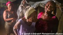 People affected by Saturday's earthquake stand under the rain of Tropical Depression Grace at a refugee camp in Les Cayes, Haiti, Monday, Aug. 16, 2021. (AP Photo/Joseph Odelyn)