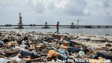 A resident passes by plastic bottles lying at the beach on the Indian Ocean