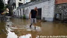 A man walks through water after heavy rain caused flooding in towns surrounding Lake Como in northern Italy, in Laglio, Italy, July 27, 2021. REUTERS/Flavio Lo Scalzo
